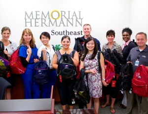 Employees from Memorial Hermann Southeast Hospital, from left, Rebecca Lilley, Mindy Rivera, Son Dinh, Lydia Garcia, Michael Collins, Chief Executive Officer Erin Asprec, Lori Gordon, Kizzy Thomas, and Glenn Burnett, donate new backpacks filled with school supplies for Operation Backpack. (PHOTO: Ariana Montelongo)