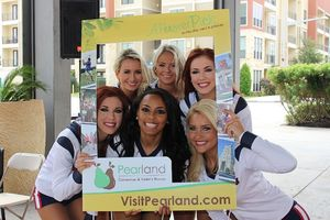 The Houston Texans Cheerleaders pose with the CVB picture frame.
