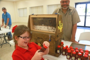 A girl visiting the Brazoria  County Beekeepers Booth checks out a bottle of honey at the Keep Pearland Beautiful Gardening Expo on August 27, 2015.